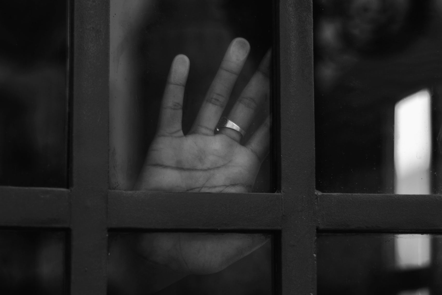 grayscale photo of persons hand on window