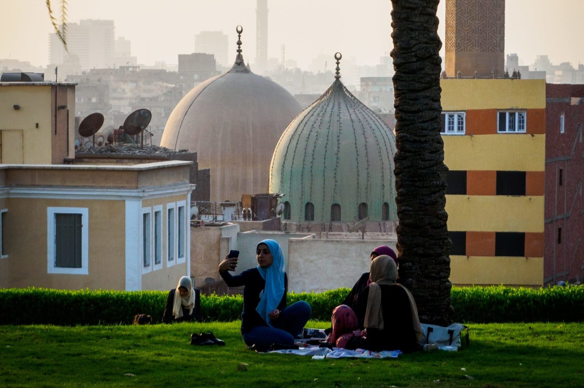 people sitting on grass near mosque